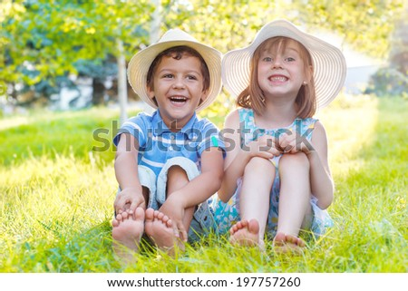 Two smiling kids sitting on green grass in a park  - stock photo