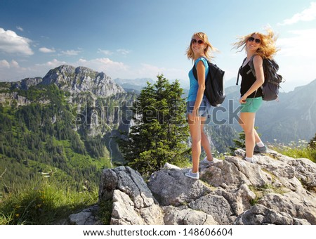 Two smiling ladies with backpacks standing on top of a mountain and looking to a camera - stock photo