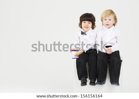 Two smiling little boy on white cube play with wireless radio on white background.