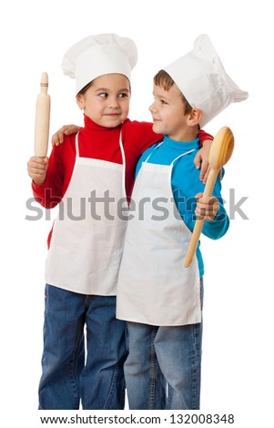 Two smiling little cooks with ladle and rolling pin, cuddling together, isolated on white