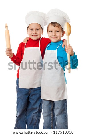 Two smiling little cooks with ladle and rolling pin, isolated on white - stock photo