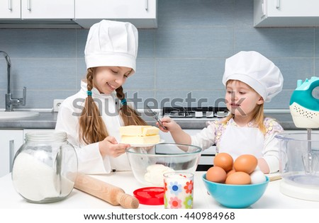 two smiling little girls-cooks cutting butter for dough on kitchen table - stock photo