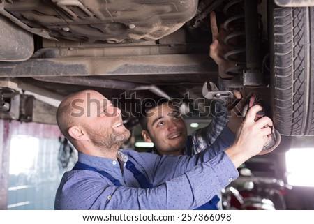 Two smiling  man fixing car tire leak  - stock photo