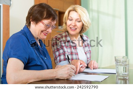 Two smiling mature woman sitting at the table and signing contracts - stock photo