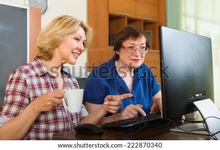 Two smiling mature women friends drinking coffee and browsing web