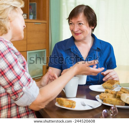 Two smiling mature women friends drinking tea and gossiping at table - stock photo