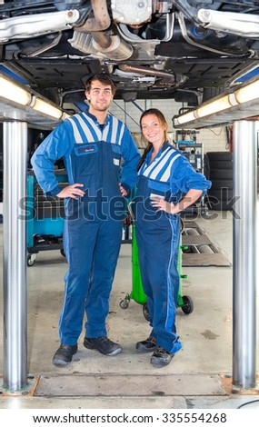 Two smiling mechanics, standing underneath a car on a bridge or car lift, looking confident and professional - stock photo