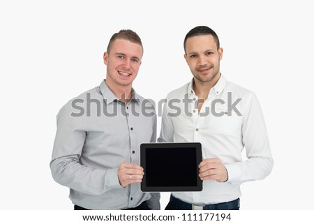 Two smiling men holding a tablet computer against a white background - stock photo