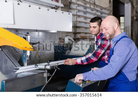 Two smiling men in uniform working on machine in PVC shop indoor