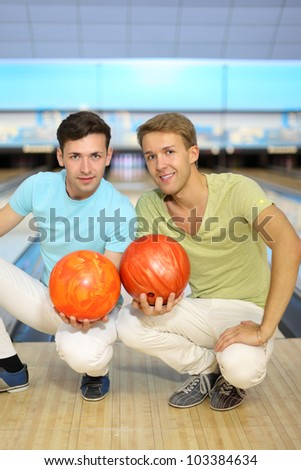 Two smiling men sit on floor with orange balls in bowling club; shallow depth of field