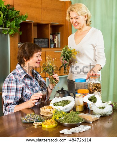Two smiling neighbors  in a room talking about medicinal herbs