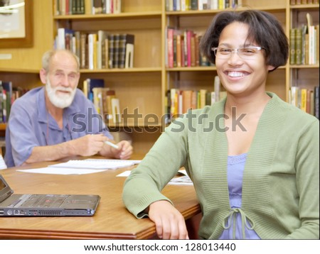 Two smiling people, European old man and African girl, in library. Shot in South Africa.
