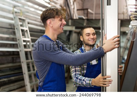 Two smiling production workmen in uniform with different PVC window profiles - stock photo