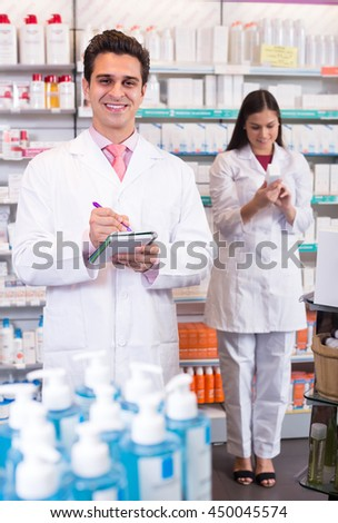 Two smiling professional pharmacists in white uniform at the work in modern pharmacy