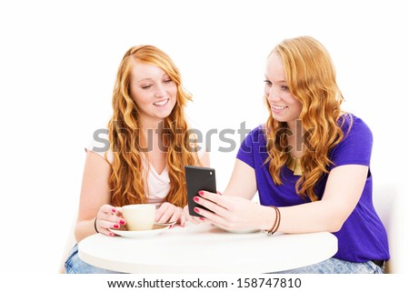 two smiling redhead women sitting at a coffee table looking at a smartphone on white background - stock photo