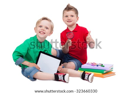 two smiling schoolboy sitting on a white background, surrounded by books and are holding a magnifying glass and tablet, with depth of field Photo - stock photo