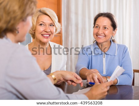 Two smiling senior ladies signing documents at bank with agent. Focus on brunette - stock photo