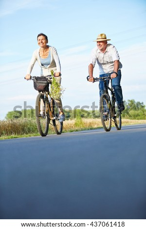 Two smiling senior people riding bikes in summer on a bike path