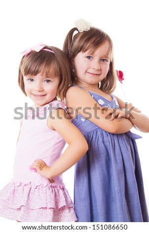 Two smiling sisters standing with their back isolated on white - stock photo