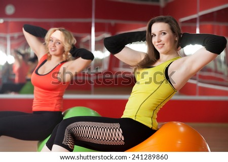 Two smiling sporty girls doing exercises for abs on fitballs