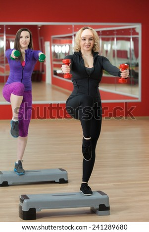 Two smiling sporty pretty girls practice step aerobics with dumbbells in sports hall - stock photo
