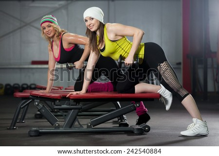 Two smiling sporty pretty girls workout in gym with dumbbells - stock photo
