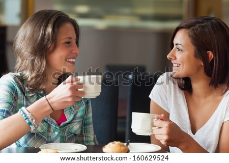 Two smiling students having a cup of coffee in college canteen - stock photo