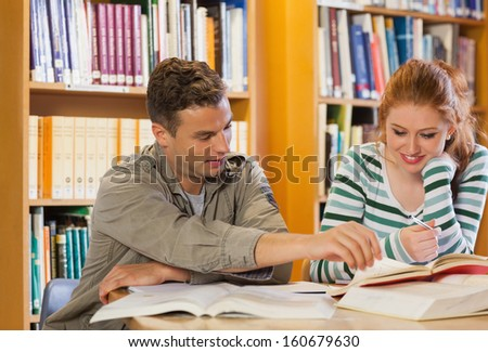 Two smiling students studying together in library
