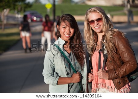Two smiling teenage female students on school campus - stock photo