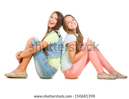 Two Smiling Teenage Girls Friends Isolated on White Background. Teenagers Sitting on a Floor Back to back and Laughing. Full Length Portrait of Students. Friendship - stock photo