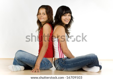 Two smiling teenage girls sitting back-to-back on the floor, caucasian/white.