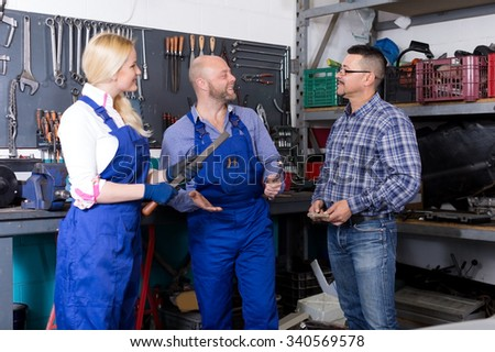 two smiling troubleshooters and adult superviser at auto repair shop. Focus on the right man
