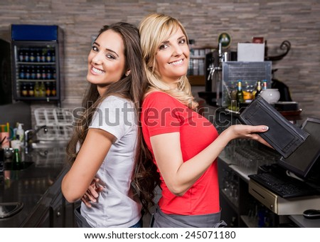 Two smiling waitress standing in a coffee shop - stock photo