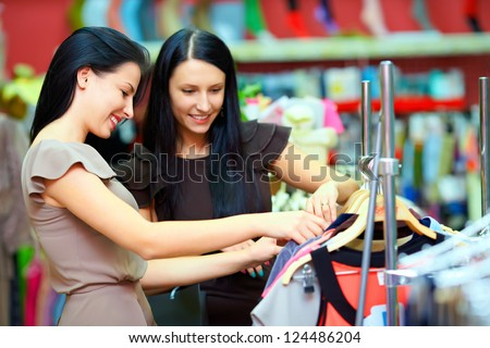 two smiling woman shopping in retail store - stock photo