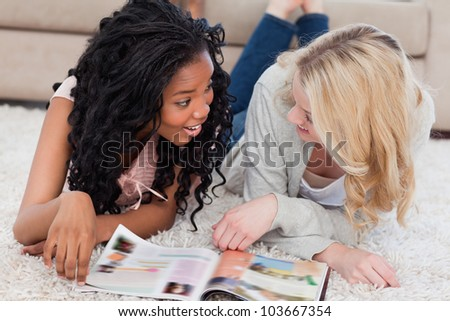 Two smiling women are lying on the floor and talking with a magazine in front of them - stock photo
