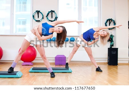 Two smiling women do stretching exercise in sports club. Fitness gym - stock photo