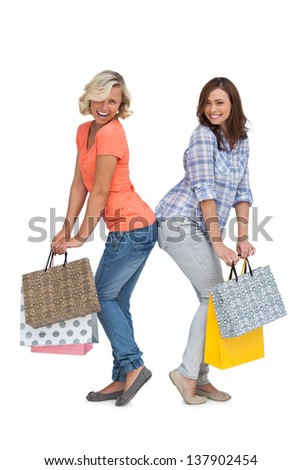 Two smiling women gesturing in front of the camera and holding shopping bags - stock photo