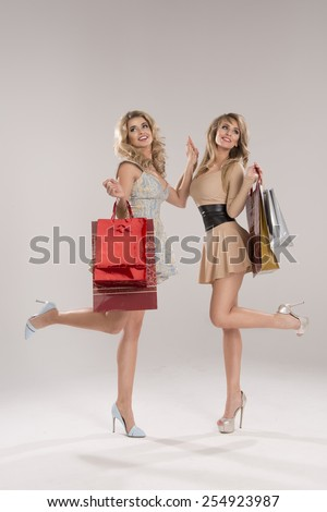 Two smiling women holding bags