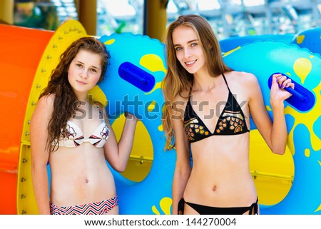 Two smiling women in bikini standing near water slide in the aqua park and holding rubber ring - stock photo
