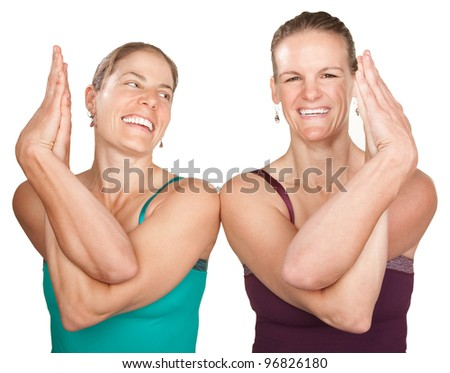 Two smiling women in Namaskar pose with twisted hands - stock photo