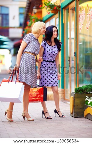 two smiling women looking in shop window, colorful exterior