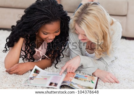 Two smiling women lying on the floor are both reading a magazine