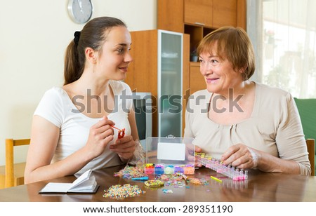 Two smiling women make bracelets with elastic rainbow loom bands - stock photo