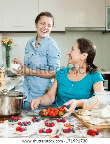 Two smiling women making perogies with berries  at home kitchen