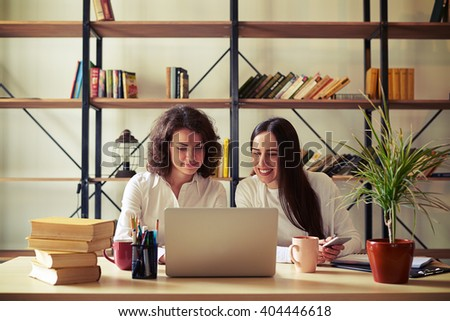 Two smiling women sitting at the table and working at a laptop and smartphones, bookshelves on a background