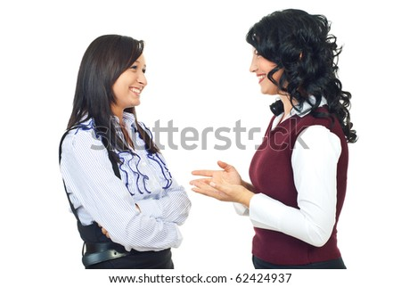 Two smiling women standing face to face and  having happy conversation while one of them giving explanation and gesticulate with hands isolated on white background