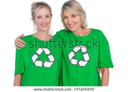 Two smiling women wearing green recycling tshirts on white background - stock photo