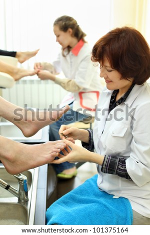 Two smiling women wearing white coats practices chiropody taking care of feet - stock photo
