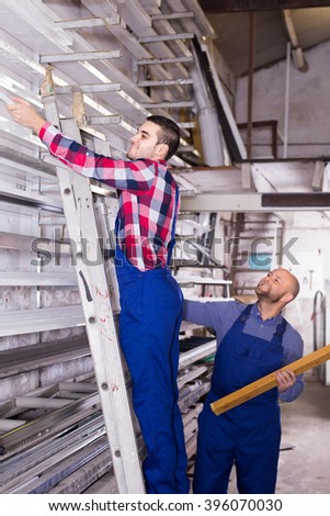 Two smiling workers in uniform choosing PVC window profile at stand - stock photo