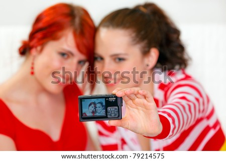 Two smiling young girlfriends sitting on sofa and taking own photo. Focus on photocamera - stock photo